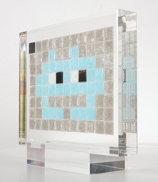 "Invader  &nbsp -  <strong>Alias NY_54</strong> (2009<strong style = 'color:#635a27'></strong>)<bR /> <font face=""Arial"">ceramic tiles in resin</font>,   <font face=""Arial"">8 1/2 x 10 1/2 x 2 inches, plus stand [21.6 x 26.7 x 5.1 cm]</font>,    ,   <font face=""Arial""><font face=""Arial"">Every Invader put up in the street can be reproduced as an Alias, which is a single replica of the original preserved in a transparent block of resin. The Alias also comes with an ID card that documents the location of the original piece. There is only one Alias produced per Invader.</font></font>,   <font face=""Arial"">NY_54 is the Alias of the Invader placed in June 2003. The price of each Alias is based on Invader's self-imposed ""score"" for difficulty and size. NY_54 is 20 points.</font>"