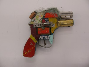 BAST -  <strong>Handgun</strong> (2013<strong style = 'color:#635a27'></strong>)<bR /> mixed media 7 x 7 x 1 1/2 in.