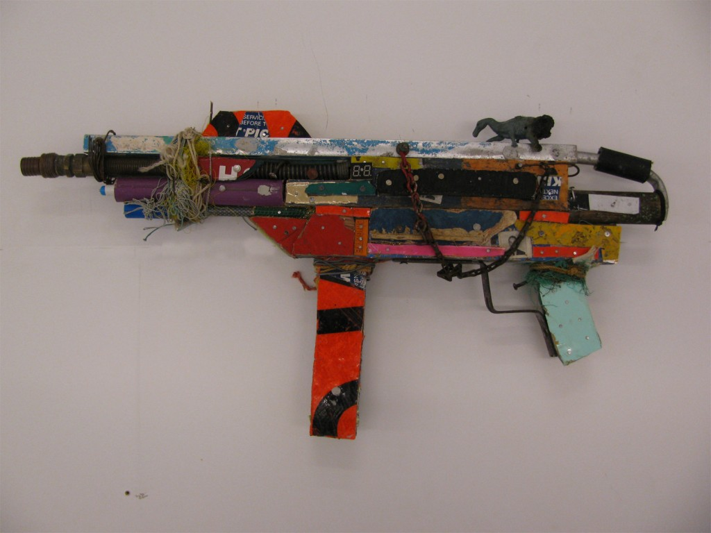 BAST -  <strong>Machine Gun</strong> (2013<strong style = 'color:#635a27'></strong>)<bR /> mixed media 12 x 25 x 2 1/2 in.