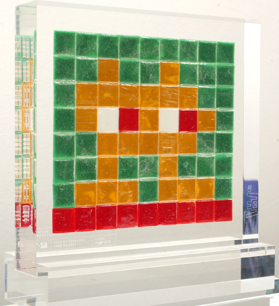 "Invader  &nbsp -  <strong>Alias NY_58</strong> (2008<strong style = 'color:#635a27'></strong>)<bR />  ,   <font face=""Arial"">ceramic tiles in resin</font>,   <font face=""Arial"">8 x 8 3/4 x 2 inches, plus stand [20.3 x 22.2 x 5.1 cm]</font>,    ,    ,    ,   <font face=""Arial""><font face=""Arial"">Every Invader put up in the street can be reproduced as an Alias, which is a single replica of the original preserved in a transparent block of resin. The Alias also comes with an ID card that documents the location of the original piece. There is only one Alias produced per Invader.</font></font>,   <font face=""Arial"">NY_58 is the Alias of the Invader placed in June 2003. The price of each Alias is based on Invader's self-imposed ""score"" for difficulty and size. NY_58 is 10 points.</font>"