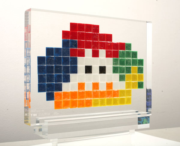 "Invader  &nbsp -  <strong>Alias NY_109</strong> (2008<strong style = 'color:#635a27'></strong>)<bR /> <font face=""Arial"">ceramic tiles in resin</font>,   <font face=""Arial"">9 1/2 x 13 3/4 x 2 inches, plus stand [24.1 x 34.9 x 5.1 cm]</font>,    ,   <font face=""Arial""><font face=""Arial"">Every Invader put up in the street can be reproduced as an Alias, which is a single replica of the original preserved in a transparent block of resin. The Alias also comes with an ID card that documents the location of the original piece. There is only one Alias produced per Invader.</font></font>,   <font face=""Arial"">NY_109 is the Alias of the Invader placed in 2007. The price of each Alias is based on Invader's self-imposed ""score"" for difficulty and size. NY_109 is 20 points.</font>"
