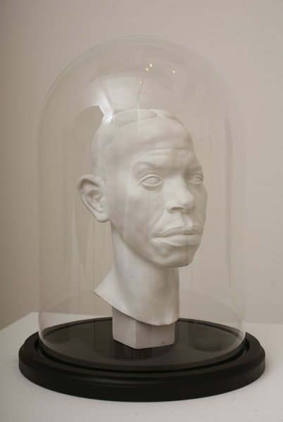 Nicola  Verlato -  <strong>Robert Johnson</strong> (2010<strong style = 'color:#635a27'></strong>)<bR /> plaster in glass display case  9 x 5.5 x 5 inches  (22.86 x 13.97 x 12.7 cm)
