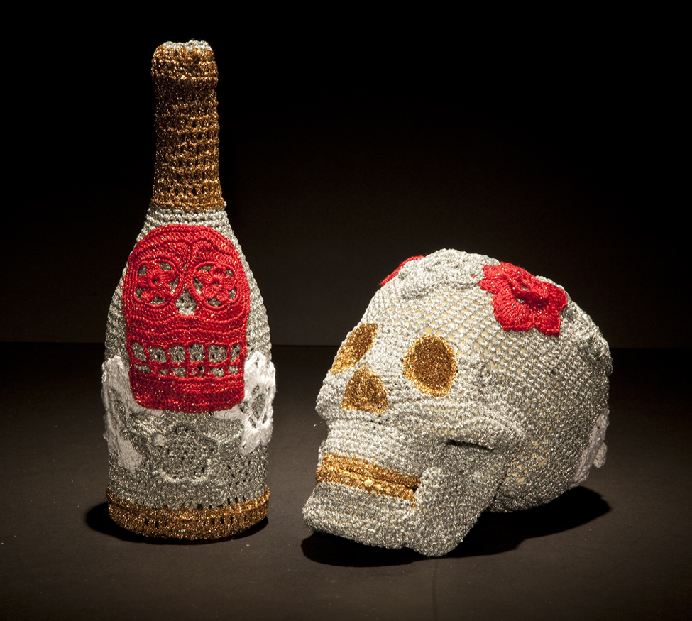 Olek  &nbsp -  <strong>New Years Eve No. 01</strong> (2013<strong style = 'color:#635a27'></strong>)<bR /> crocheted acrylic yarn and metallic ribbon on bottle and plastic skull,   bottle: 11.75 x 3.75 x 3.75 inches  skull: 6.25 x 5.75 x 8.5 inches