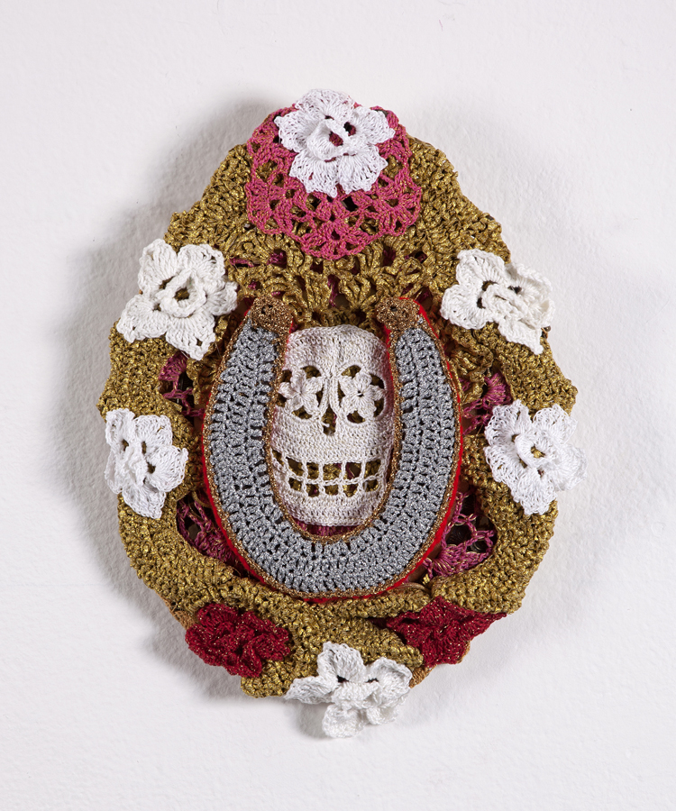 Olek  &nbsp -  <strong>Skull and Horseshoe</strong> (2013<strong style = 'color:#635a27'></strong>)<bR /> crocheted acrylic yarn, metallic ribbon and horseshoe on canvas,   13.5 x 10.5 x 2.5 inches  (34.3 x 26.67 x 6.35 cm)