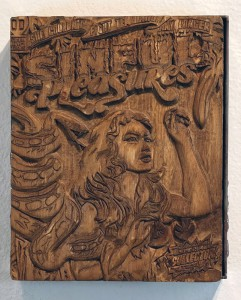Faile   -  <strong>Sinful Collector Carving</strong> (2014<strong style = 'color:#635a27'></strong>)<bR /> silkscreen ink on hand carved wood, steel frame,   8 x 12 x 3 inches  (20.32 x 30.48 x 7.62 cm)