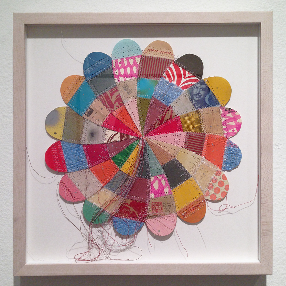 Thomas  Campbell -  <strong>Medium Flower</strong> (2014<strong style = 'color:#635a27'></strong>)<bR /> paper, acrylic, packing envelope, thread, acrylic, spray paint, pencil, rice bags, money, resin and fiberglass,   13 x 13.5 x 1.75 inches  (33.02 x 34.29 x 4.45 cm),   14 1/8 x 13 7/8 inches, framed