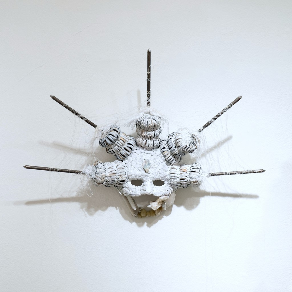 Lucien  Shapiro -  <strong>Light Hides Darkness Mask</strong> (<strong style = 'color:#635a27'></strong>)<bR /> bottle caps, nails, wire, string, thread, quartz, selenite, celestite, sculpting putty, resin, epoxy,   18.5 x 24 x 5 inches  (46.99 x 60.96 x 12.7 cm)