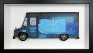 Drew Leshko -  <strong>Blue Buff LLV</strong> (2016<strong style = 'color:#635a27'></strong>)<bR /> paper, enamel, dry pigments, acrylic, plastic, clay, wire, inkjet print, toy hubcaps. Framed in shadowbox without glass, 16 x 27.5 x 3 inches, (40.64 x 69.85 x 7.62 cm)