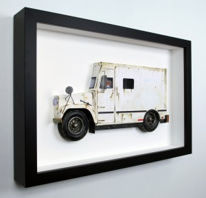 Drew Leshko -  <strong>Brinks Truck (side)</strong> (2016<strong style = 'color:#635a27'></strong>)<bR /> paper, enamel, dry pigments, acrylic, plastic, wire, inkjet print, toy wheels. Framed in shadowbox without glass,