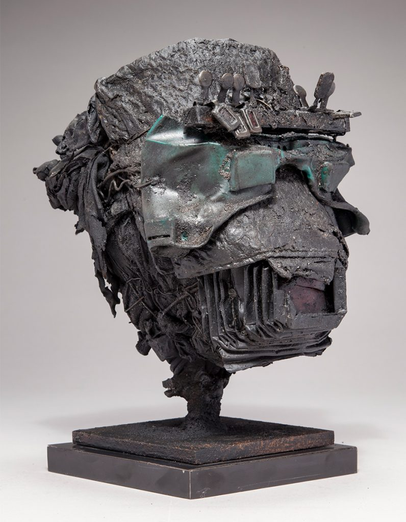Ronald Gonzalez -  <strong>Head</strong> (2017<strong style = 'color:#635a27'></strong>)<bR /> manipulated found objects, wax, wire, soot, metal filings over welded steel, 	 11.5 x 8 x 8 inches $2,250