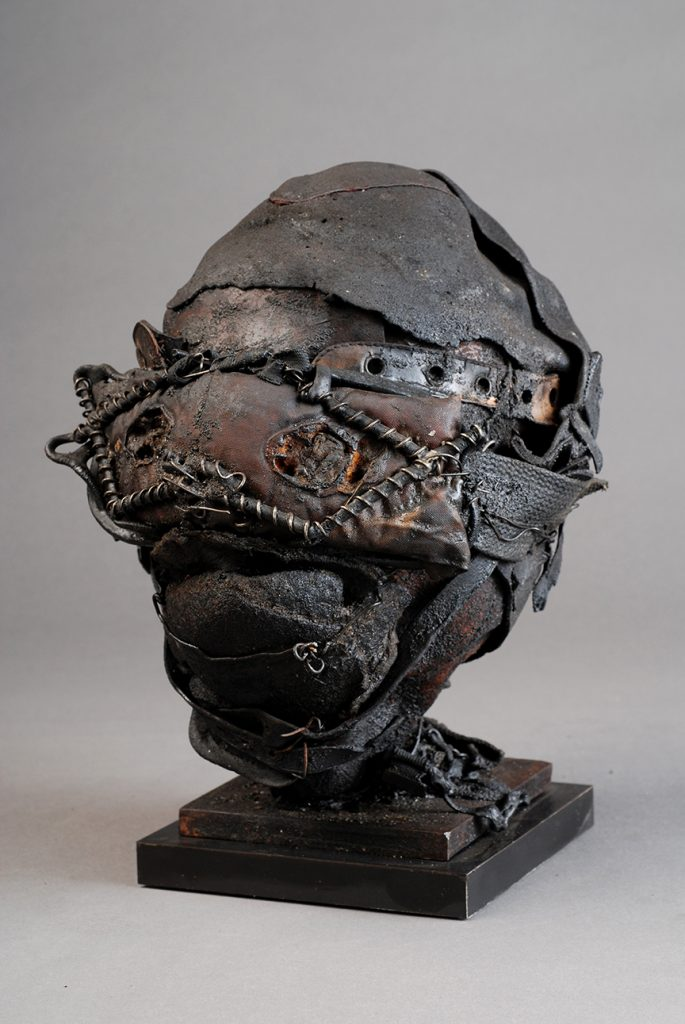 Ronald Gonzalez -  <strong>Masked Head</strong> (2017<strong style = 'color:#635a27'></strong>)<bR /> manipulated found objects, wax, wire, soot, metal filings over welded steel, 	 12 x 10 x 10 inches $2,250