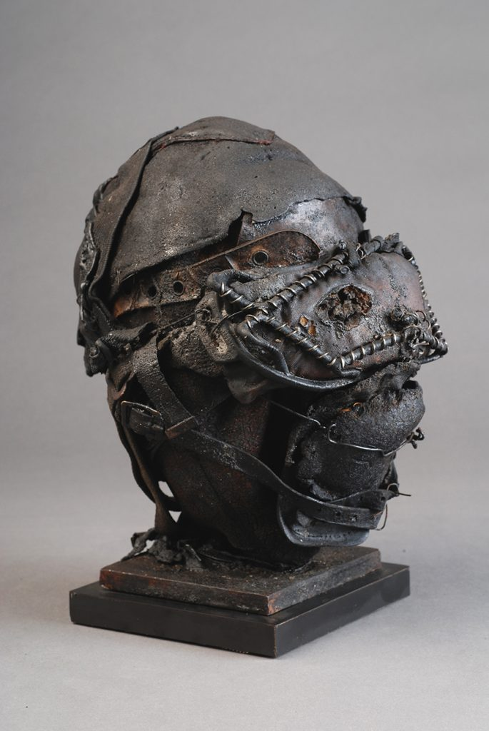 Ronald Gonzalez -  <strong>Masked Head (side)</strong> (2017<strong style = 'color:#635a27'></strong>)<bR /> manipulated found objects, wax, wire, soot, metal filings over welded steel, 	 12 x 10 x 10 inches $2,250
