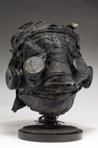 Ronald Gonzalez -  <strong>Darkly (side)</strong> (2018<strong style = 'color:#635a27'></strong>)<bR /> black leather, found objects, wire, wax, carbon, screws and metal filings over welded steel armatures, 12 x 10 x 9 inches