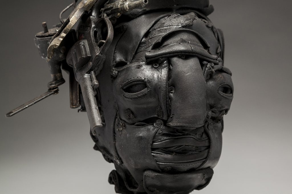 Ronald Gonzalez -  <strong>Dead Air (detail)</strong> (2018<strong style = 'color:#635a27'></strong>)<bR /> black leather, found objects, wire, wax, carbon, screws and metal filings over welded steel armatures, 18 x 10 x 8 inches