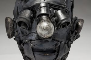 Ronald Gonzalez -  <strong>Empty Sockets (detail)</strong> (2018<strong style = 'color:#635a27'></strong>)<bR /> black leather, found objects, wire, wax, carbon, screws and metal filings over welded steel armatures, 11 x 9 x 10 inches