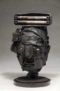 Ronald Gonzalez -  <strong>Lamp</strong> (2018<strong style = 'color:#635a27'></strong>)<bR /> black leather, found objects, wire, wax, carbon, screws and metal filings over welded steel armatures, 13 x 8 x 7 inches