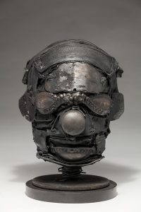 Ronald Gonzalez -  <strong>Mask</strong> (2018<strong style = 'color:#635a27'></strong>)<bR /> black leather, found objects, wire, wax, carbon, screws and metal filings over welded steel armatures, 10 x 8 x 8 inches