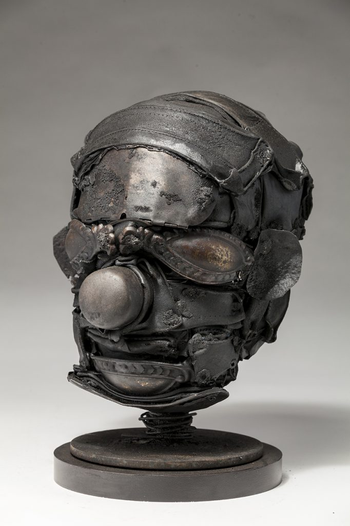 Ronald Gonzalez -  <strong>Mask (side)</strong> (2018<strong style = 'color:#635a27'></strong>)<bR /> black leather, found objects, wire, wax, carbon, screws and metal filings over welded steel armatures, 10 x 8 x 8 inches