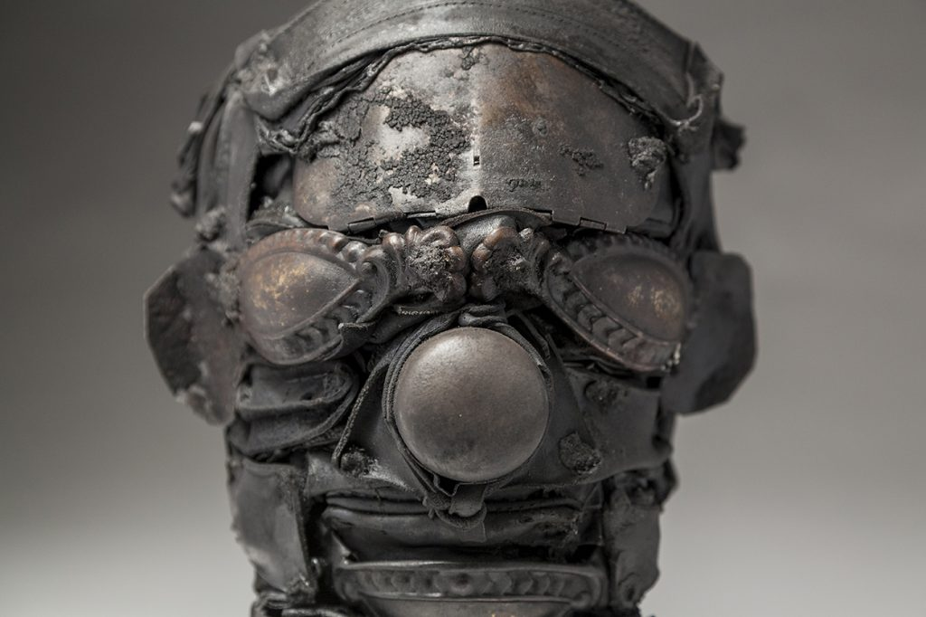 Ronald Gonzalez -  <strong>Mask (detail)</strong> (2018<strong style = 'color:#635a27'></strong>)<bR /> black leather, found objects, wire, wax, carbon, screws and metal filings over welded steel armatures, 10 x 8 x 8 inches