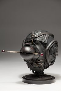 Ronald Gonzalez -  <strong>Messenger (side)</strong> (2018<strong style = 'color:#635a27'></strong>)<bR /> black leather, found objects, wire, wax, carbon, screws and metal filings over welded steel armatures, 11 x 9 x 12 inches