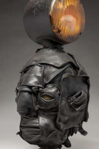 Ronald Gonzalez -  <strong>Signal (side)</strong> (2018<strong style = 'color:#635a27'></strong>)<bR /> black leather, found objects, wire, wax, carbon, screws and metal filings over welded steel armatures, 16 x 7 x 8 inches