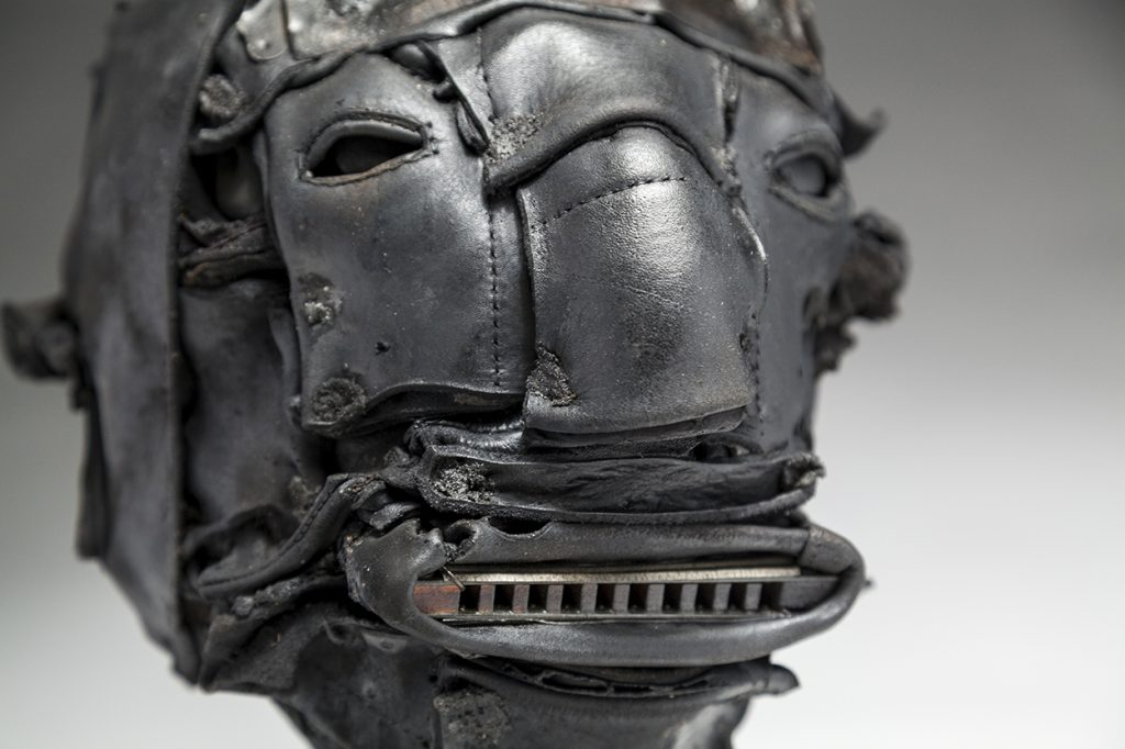 Ronald Gonzalez` -  <strong>Tune (detail)</strong> (2018<strong style = 'color:#635a27'></strong>)<bR /> black leather, found objects, wire, wax, carbon, screws and metal filings over welded steel armatures, 12 x 8 x 10 inches