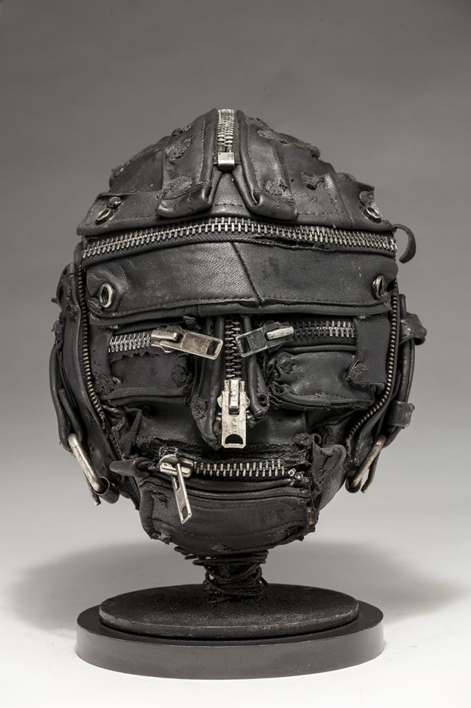 Ronald Gonzalez -  <strong>Zipped</strong> (2018<strong style = 'color:#635a27'></strong>)<bR /> black leather, found objects, wire, wax, carbon, screws and metal filings over welded steel armatures, 11 x 9 x 9 inches