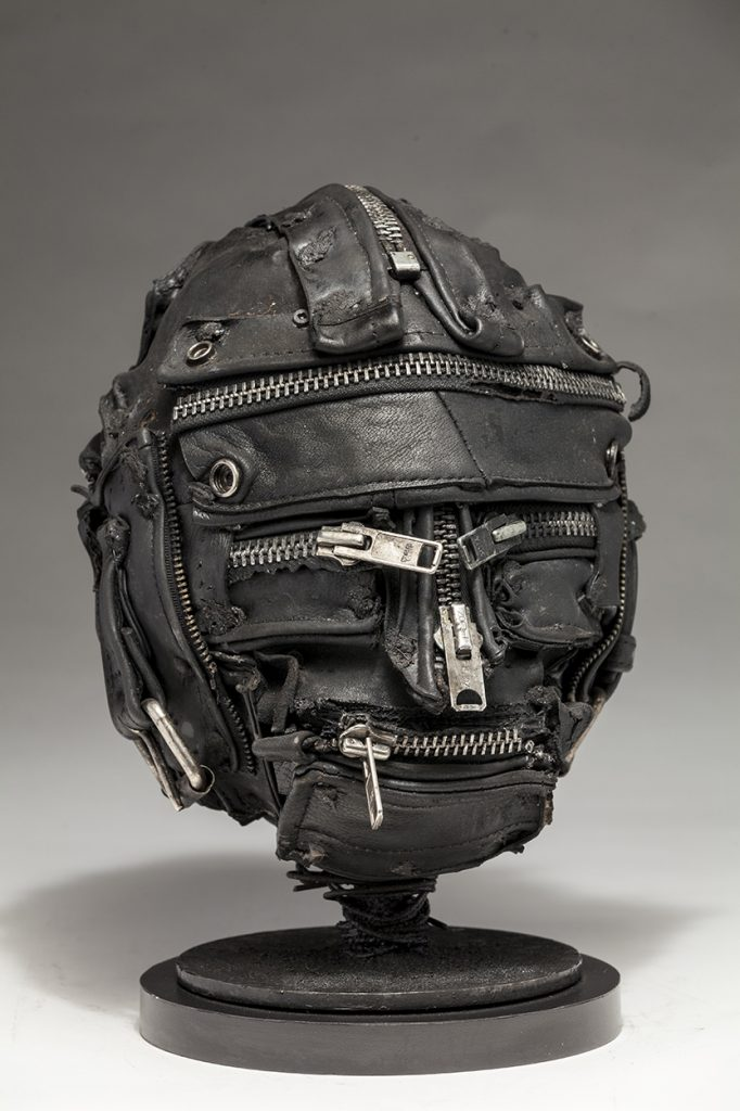Ronald Gonzalez -  <strong>Zipped (side)</strong> (2018<strong style = 'color:#635a27'></strong>)<bR /> black leather, found objects, wire, wax, carbon, screws and metal filings over welded steel armatures, 11 x 9 x 9 inches