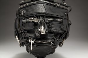 Ronald Gonzalez -  <strong>Zipped (detail)</strong> (2018<strong style = 'color:#635a27'></strong>)<bR /> black leather, found objects, wire, wax, carbon, screws and metal filings over welded steel armatures, 11 x 9 x 9 inches
